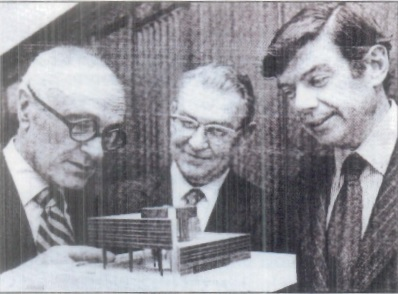 Philip Johnson and John Burgee flank General American President Armand C. Stalnaker as they examine a model of the new headquarters building in 1977.