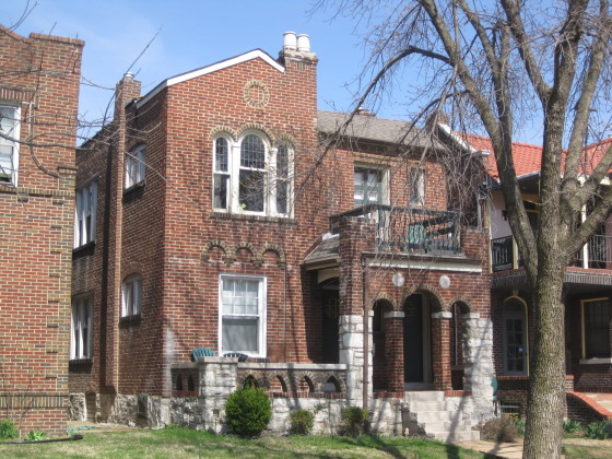 "The district's ""garden"" qualities are evident in this dwelling on Flad Avenue: brick and stone designed to look handmade, landscaped front yard, front porch."